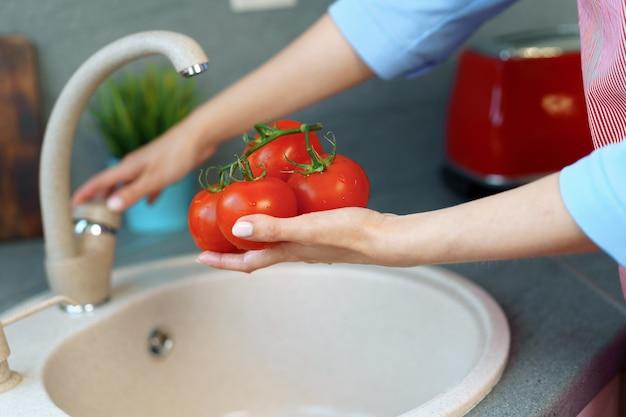 シンクでトマトを洗う女性の写真をクローズアップ