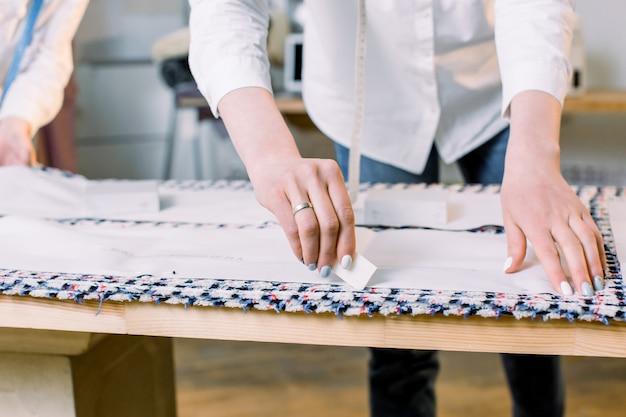 縫製パターンで作業する仕立て屋の女性の手のクローズアップ写真。チョークで生地に線を引き、職場で調整