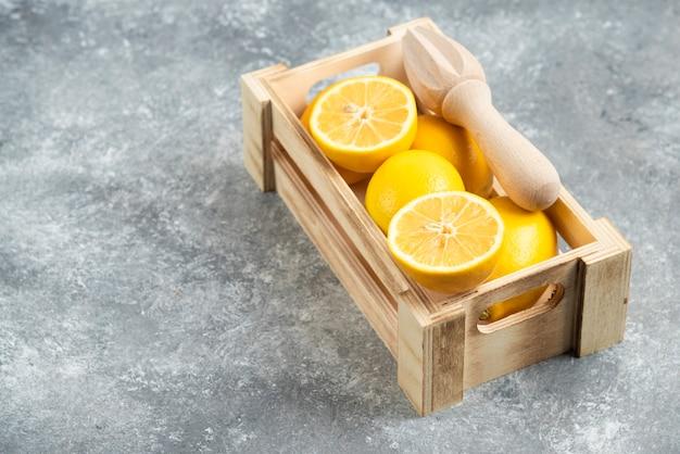 신선한 레몬으로 가득한 나무 상자의 사진을 닫습니다.
