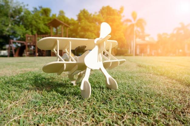 Закрыть фото деревянный игрушечный самолет против на траве
