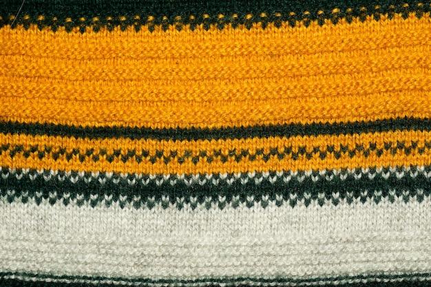 Закройте вверх по фото желтой, зеленой и белой полосатой вязанной текстуры свитера как абстрактный фон.