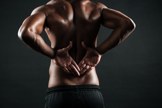 彼の背中に痛みを感じている若いアフリカスポーツ男のクローズアップ写真