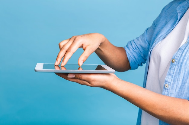 디지털 태블릿을 들고 텍스트, 로고 또는 광고에 대 한 복사 공간이 격리 된 파란색 배경 위에 서 웃 고 곱슬 아프리카 머리를 가진 젊은 미국 학생 여자의 클로즈업 사진.