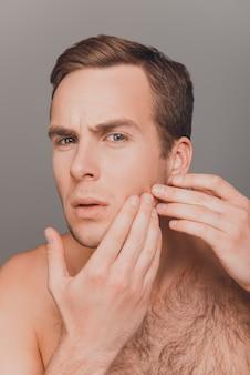 Крупным планом фото молодого привлекательного человека, смотрящего на его кожу