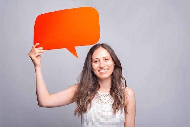 Крупным планом фото молодой очаровательной женщины, держащей красный пустой речи пузырь