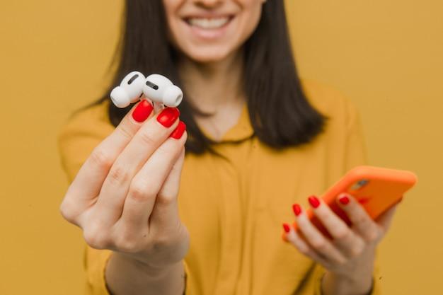 Крупным планом фото молодой женщины держит earpods и смартфон выглядит таким добрым и счастливым. носит желтую рубашку, изолированный желтый цвет фона.