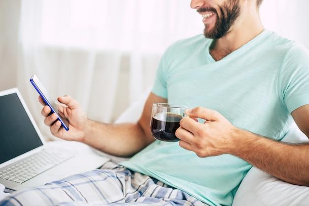 ノートパソコンとスマートフォンを持っている若い男の写真をクローズアップ寝室でコーヒーを飲みます。
