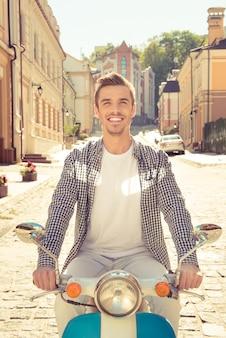 通りでスクーターに乗って眼鏡をかけた若い男の写真を閉じる