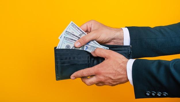 アメリカの財布とドルの束で若い成功した実業家の手の写真をクローズアップ