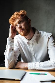 若い思考の巻き毛のリードヘッド男、彼の職場の上に座ってのクローズアップ写真