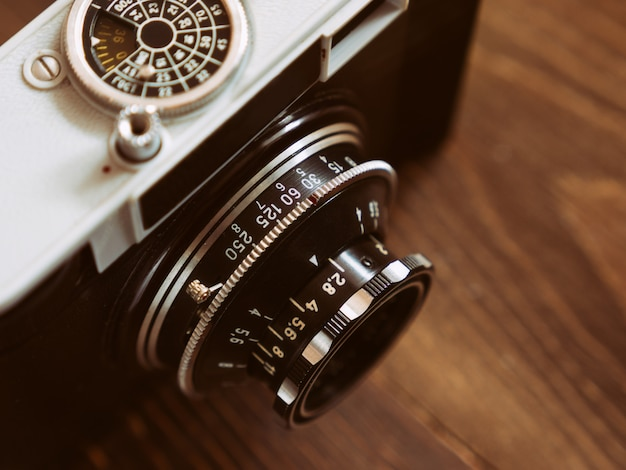Close up photo of old vintage camera lens over wooden table. selective focus