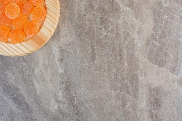 Chiuda sulla foto delle caramelle arancioni sul piatto di legno sull'angolo della foto.