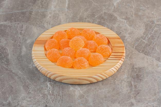 Foto ravvicinata di caramelle di gelatina d'arancia su piatto di legno.