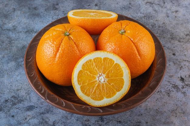 Primo piano foto di arance biologiche sulla piastra su grigio.
