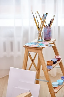 Close-up photo of paints, paintbrushes, easel and canvas in light art studio room