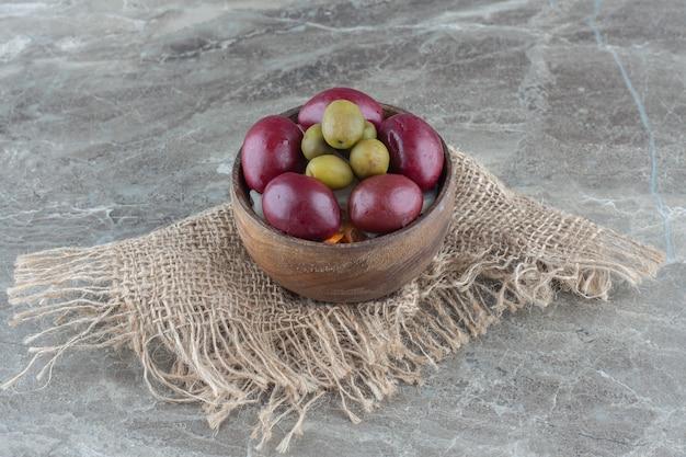 Close up foto di palme e olive in ciotola di legno su sfondo grigio.
