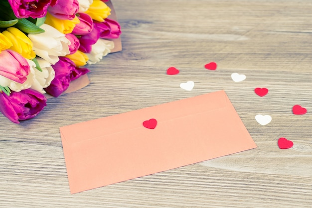 Close-up photo of pastel red envelope with tender poetry inside lying on wooden table near colorful bright tulips