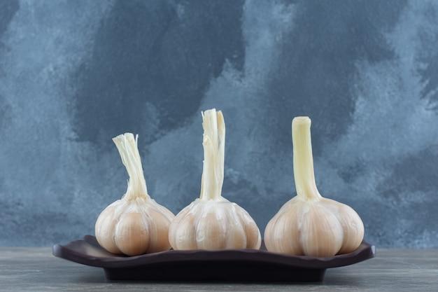 Close up foto di aglio sottaceto sulla banda nera su sfondo grigio.