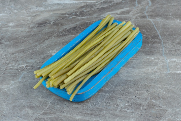 Close up photo of pickled green sticks on wooden board.
