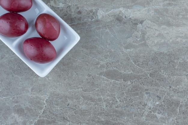 Chiuda sulla foto della palma marinata sul piatto bianco sopra fondo grigio.