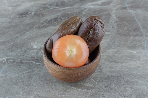 Foto ravvicinata di pomodori sottaceto e melanzane in una ciotola di legno.