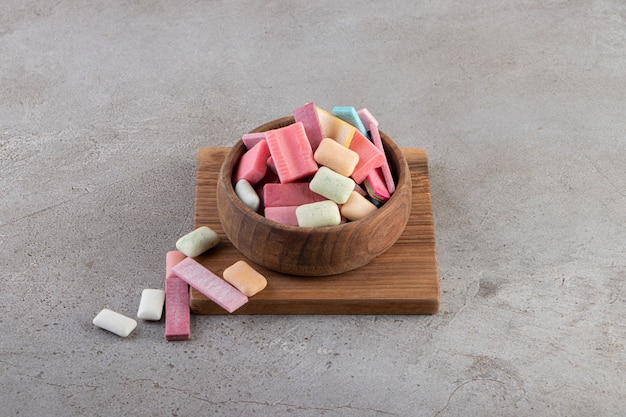 Close up photo of pile of colorful sweet gums in wooden bowl