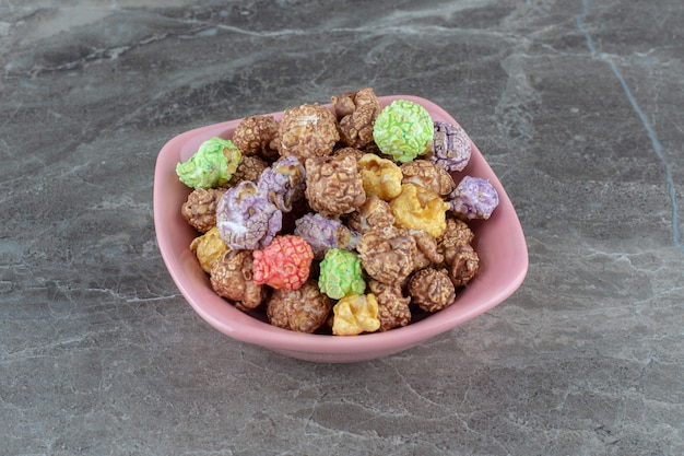 Foto ravvicinata di una pila di caramelle colorate fatte in casa in una ciotola rosa.