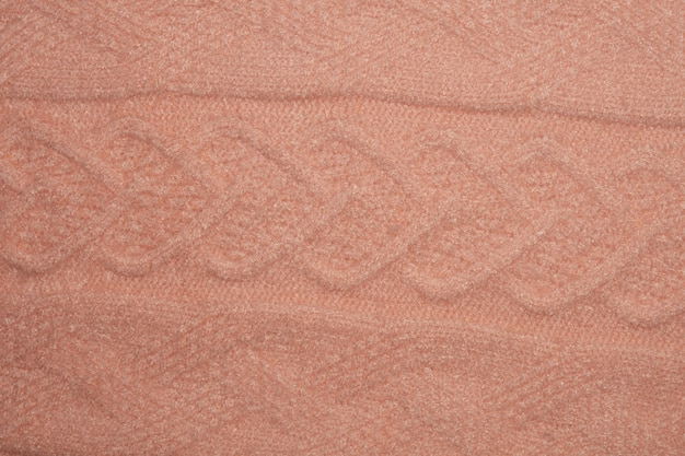 Close up photo of pink knitted sweater texture as abstract background.