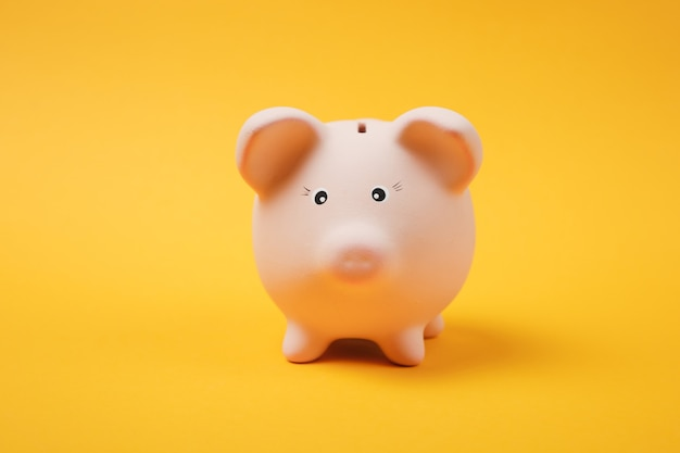 Close up photo of pink piggy money bank isolated on bright yellow wall background. money accumulation, investment, banking or business services, wealth concept. copy space advertising mock up.