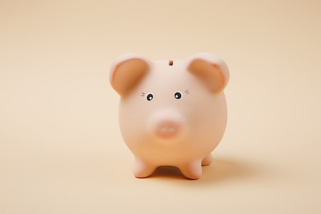 Close up photo of pink piggy money bank isolated on pastel beige wall background. money accumulation, investment, banking or business services, wealth concept. copy space advertising mock up.