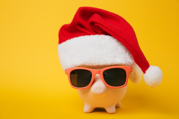 Close up photo of pink piggy money bank with sunglasses christmas hat isolated on yellow wall background. money accumulation investment banking services wealth concept. copy space advertising mock up.