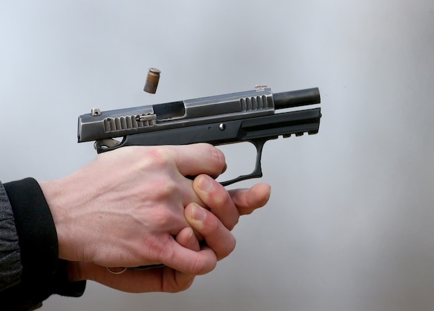 Close-up photo of a pistol shooting with two hands, the shells emanating from the shutter and blue smoke.