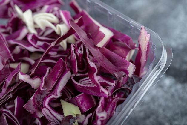 Foto ravvicinata di un contenitore di plastica pieno di cavolo viola tritato. foto macro.