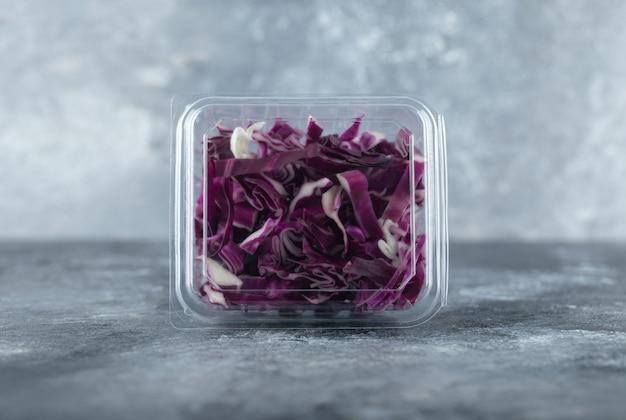 Foto ravvicinata di un contenitore di plastica pieno di cavolo viola tritato o sfondo grigio.