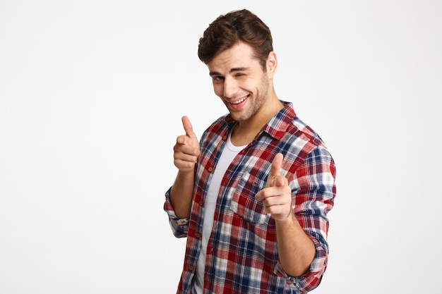 Close-up photo of playful shaven young man in checkered shirt pointing with two fingers