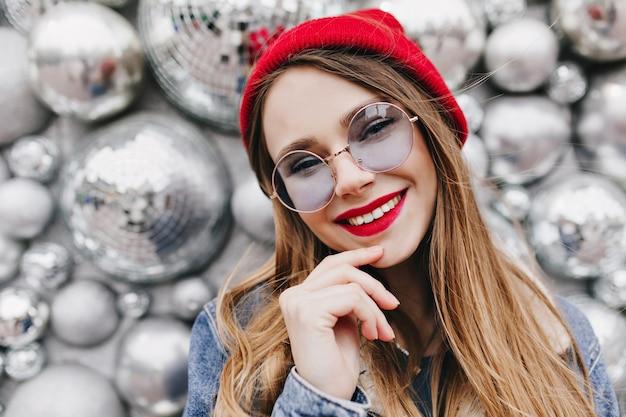 Foto del primo piano della ragazza soddisfatta con trucco luminoso che posa vicino alle palle della discoteca. ritratto di affascinante giovane donna bianca in abbigliamento casual sorridente