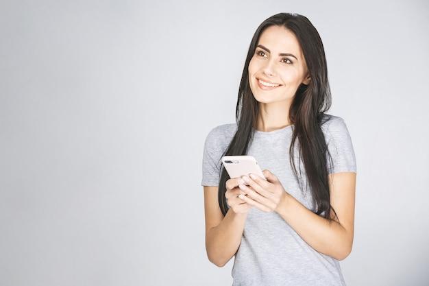 Крупным планом фото портрет веселой дамы с помощью смартфона в руке