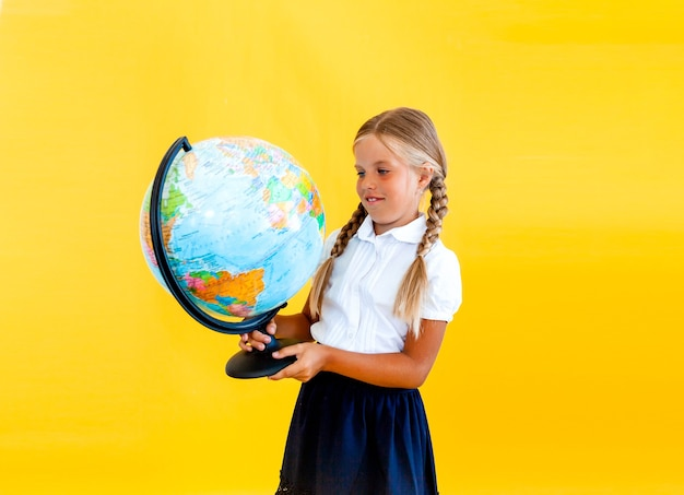 地球儀を手に持って面白いかわいい笑って驚いた女の子の写真の肖像画を閉じる