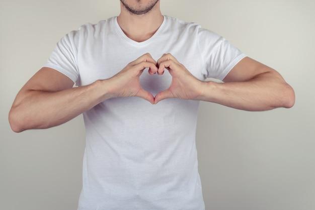 회색 회색 벽 복사 공간에 고립 된 가슴에 마음을 만드는 잘 생긴 귀여운 좋은 매력적인 근육 질의 남자의 사진 초상화를 닫습니다