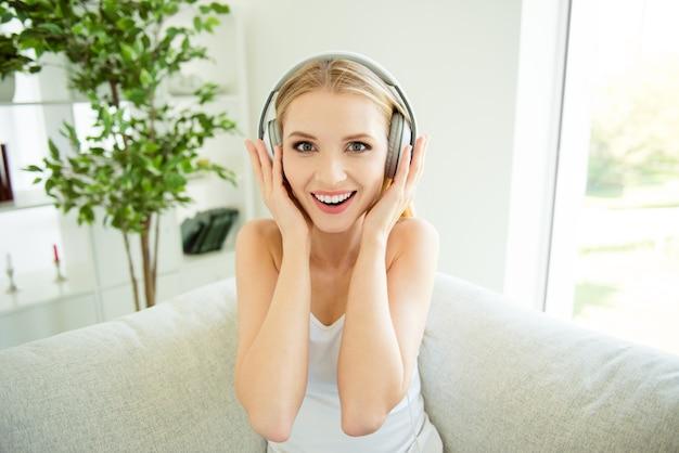 Крупным планом фото портрет леди, слушающей музыку в больших наушниках