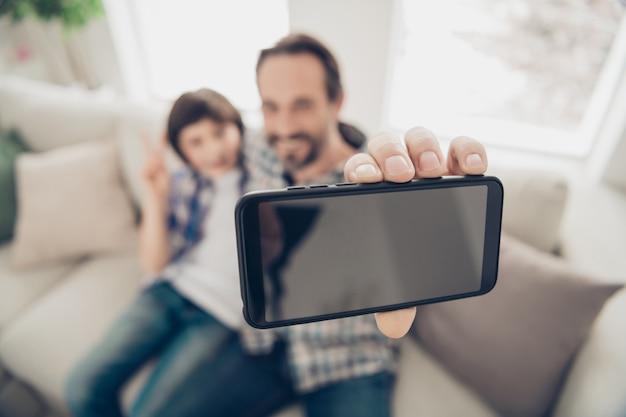 Крупным планом фото портрет позитивного расслабленного приятного радостного папы, делающего селфи со своим младшим сыном по телефону, сидящим на удобном диване, отдыхающим свободное время в выходные в гостиной дома