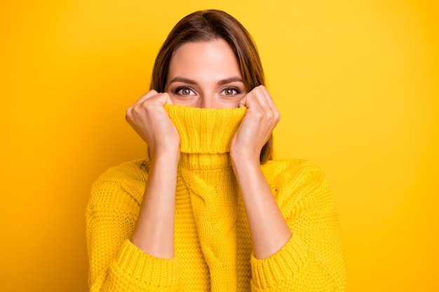 Close up photo of positive cheerful girl hide her face lips feel shy on cold temperature weather free time wear modern soft pullover isolated over bright color wall