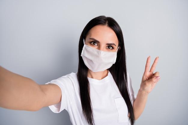 Крупным планом фото позитивная девушка делает селфи-шоу vsign имеет медицинскую маску, настоящая самоизоляция, остановить распространение вируса короны, блоггер, влиятельный человек, носить белую футболку, изолированный серый цвет фона