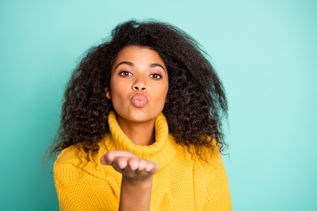 Close up photo of pretty dark skin feminine lady holding open palm raised sending air kiss to handsome guy wear yellow knitted pullover isolated teal color wall