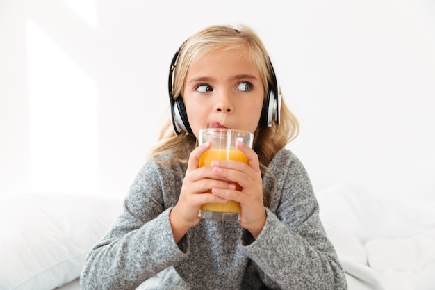 Close-up photo of pretty little girl in headphones licking while drinking orange juice, looking aside