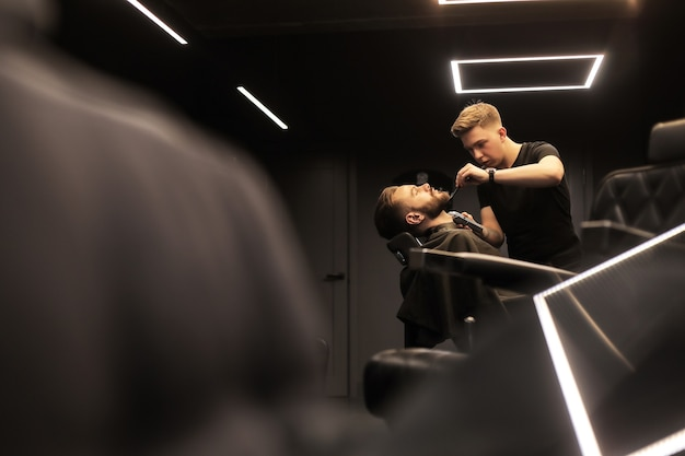 Close-up photo of a professional hairstylist, who is grooming beard of his young client, who is looking in the mirror during the procedure.