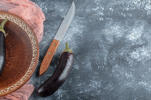 Close up photo of raw aubergine and knife on grey background.