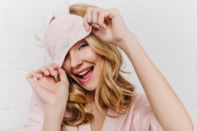 Close-up photo of refined blonde girl with elegant manicure posing with cute sleep mask. pretty caucasian curly woman in pink outfit fooling around in morning.