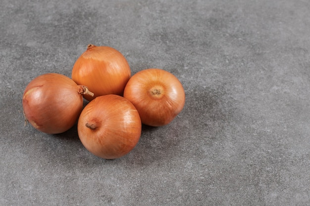 Close up photo of ripe onions on grey table.