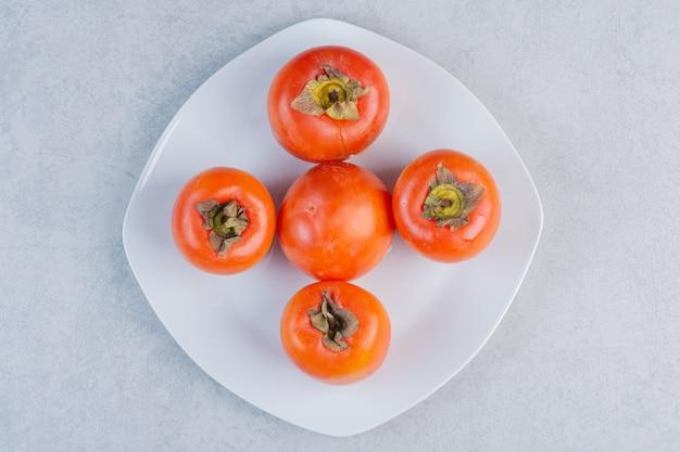 Close up foto di maturi frutti di cachi arancio. cachi freschi sulla zolla bianca.